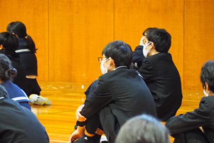 体育館で間隔を開けて座る中学生