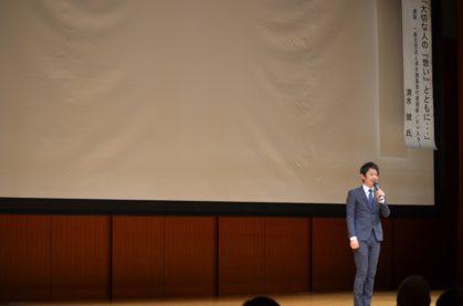 男性、スーツ姿、講演会、壇上で話す人