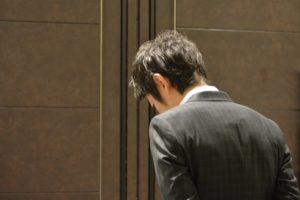 男性の後ろ姿、ドアの前、物思いに耽る