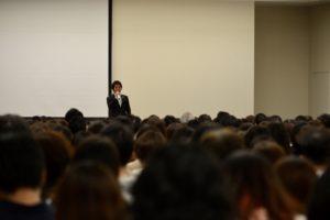 講演会、多くの聴衆、前で話す人