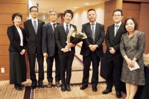 集合写真、中央で花束を持つ男性