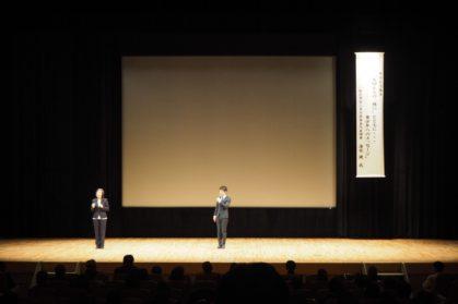 講演会、壇上で話す男性、手話通訳士