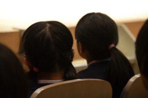 中学生の後ろ姿、講演を聞いている