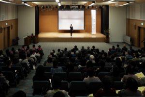 講演会、多くの聴衆、壇上の男性